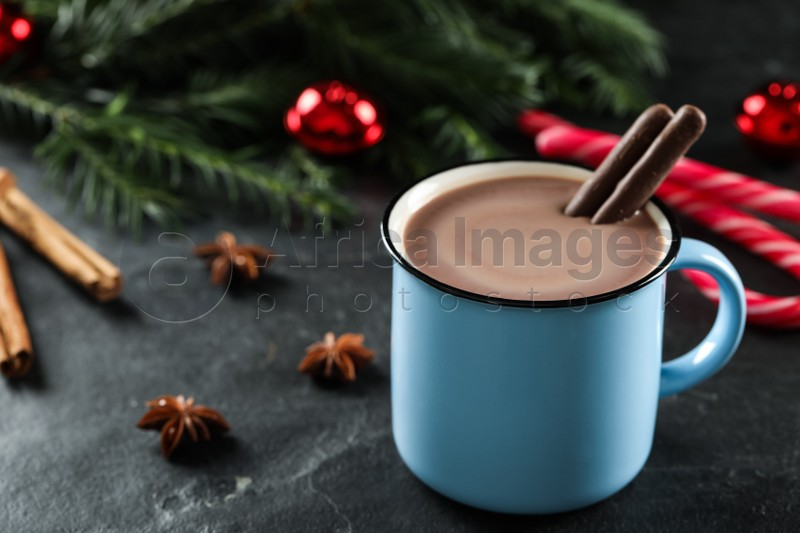 Delicious hot chocolate with cocoa sticks near Christmas decor on black table, closeup. Space for text
