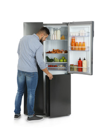 Young man opening refrigerator on white background