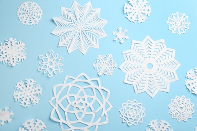 Many paper snowflakes on light blue background, flat lay