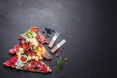 Fir tree shaped board with different appetizers and sauce on black table, flat lay. Space for text