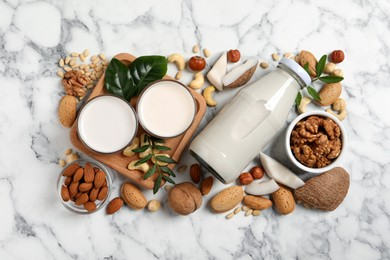 Vegan milk and different nuts on white marble table, flat lay