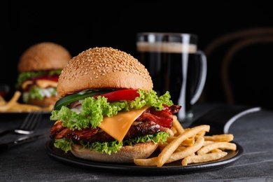Fresh juicy bacon burger and fries on grey table