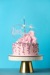 Beautifully decorated birthday cake with party decor on turquoise wooden table