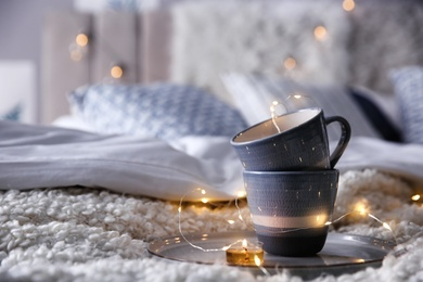 Cups, burning candle and garland on bed in room, space for text. Interior elements