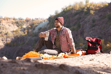 Male camper with thermos sitting on sleeping bag in wilderness