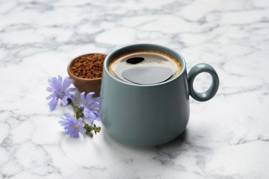 Cup of delicious chicory drink, granules and flowers on white marble table