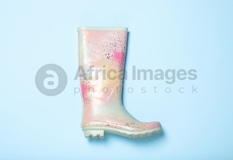 Colorful rubber boot on light blue background, top view