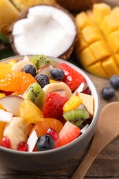 Delicious fresh fruit salad in bowl on wooden table, closeup