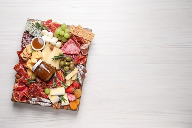 Assorted appetizer served on white wooden table, top view. Space for text