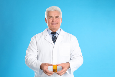 Senior pharmacist with pills on light blue background