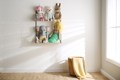Shelf with cute toys on light wall indoors. Baby room interior element