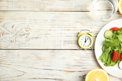 Alarm clock and healthy food on white wooden table, flat lay with space for text. Meal timing concept