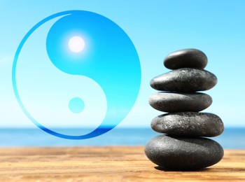 Stack of stones on wooden table outdoors and Ying Yang symbol. Feng Shui philosophy