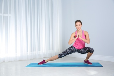 Young woman doing fitness exercises at home. Space for text