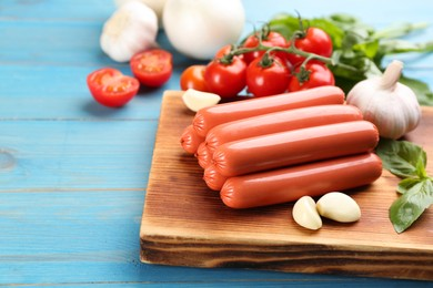 Fresh raw vegetarian sausages and vegetables on light blue wooden table, closeup