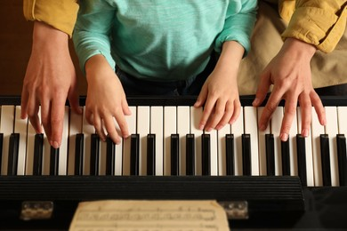 Young woman with child playing piano, top view. Music lesson