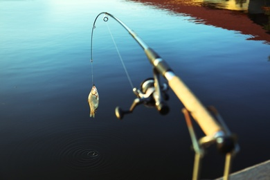 Fishing rod with caught fish at lake on sunny day