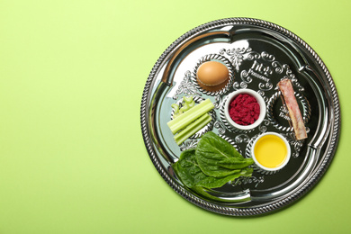 Passover Seder plate (keara) with symbolic meal on green background, top view. Pesah celebration