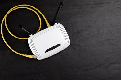 Modern Wi-Fi router on black background, top view. Space for text