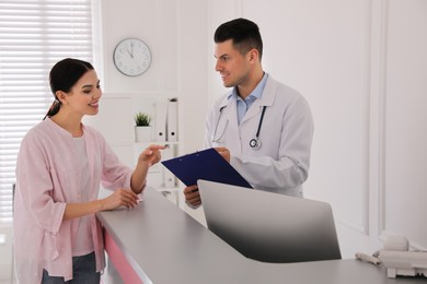 Doctor working with patient at reception in hospital