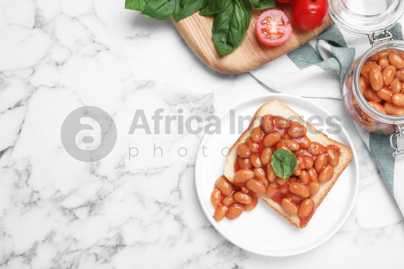 Toast with delicious canned beans on white marble table, flat lay. Space for text