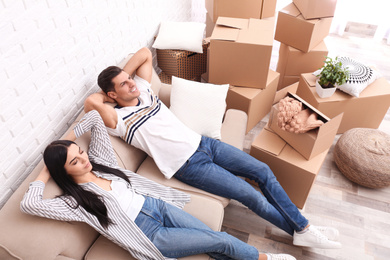 Happy couple resting in room with cardboard boxes on moving day, above view