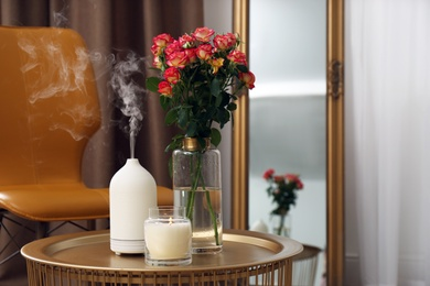 Aroma oil diffuser, burning candle and beautiful roses on table indoors, space for text. Interior elements