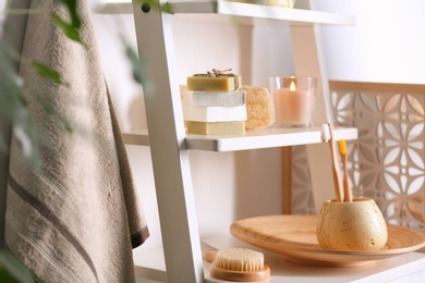 Soap and toiletries on wooden shelves in bathroom