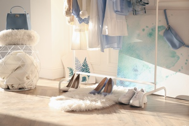 Faux fur rug with stylish women's shoes indoors. Interior design