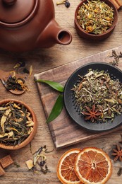 Flat lay composition with different dry teas on wooden table