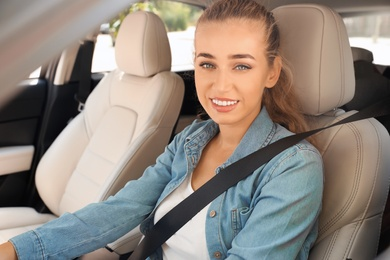 Female driver with fastened safety belt in car