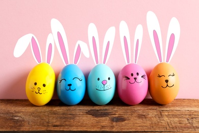 Colorful eggs as Easter bunnies on wooden table against pink background