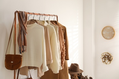 Rack with stylish women's clothes in dressing room. Modern interior design