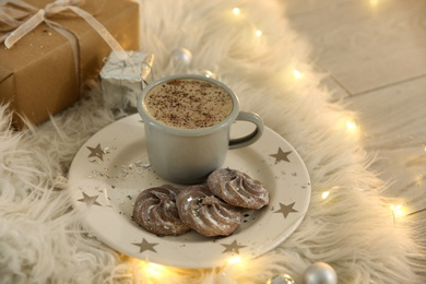 Tasty hot drink, cookies, gift and Christmas lights on fur