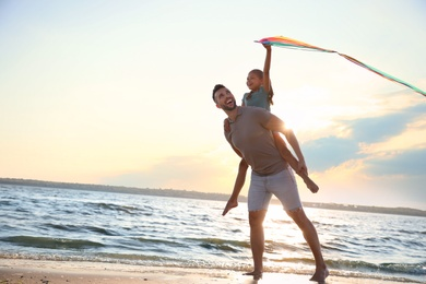 Happy father and his child playing with kite on beach near sea. Spending time in nature