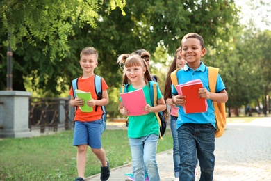 Cute little children with backpacks going to school