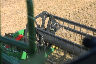 Modern combine harvester in agricultural field, closeup view of reel