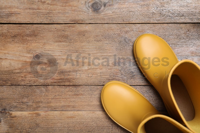 Yellow rubber boots on wooden background, top view. Space for text