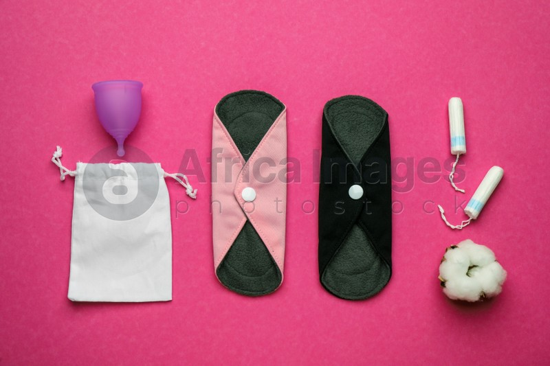 Reusable cloth pads and menstrual cup near disposable tampons on pink background, flat lay