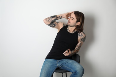 Young man with tattoos on body against white background
