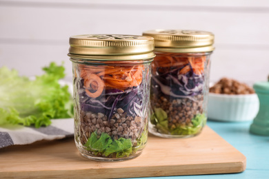 Glass jars with healthy meal on light blue wooden table