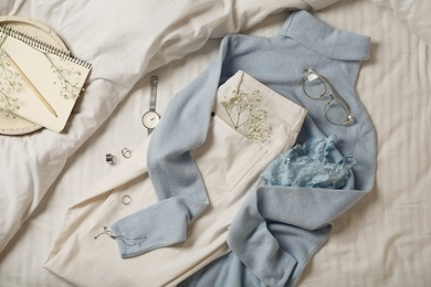 Stylish look with cashmere sweater, flat lay. Women's clothes and accessories on bed