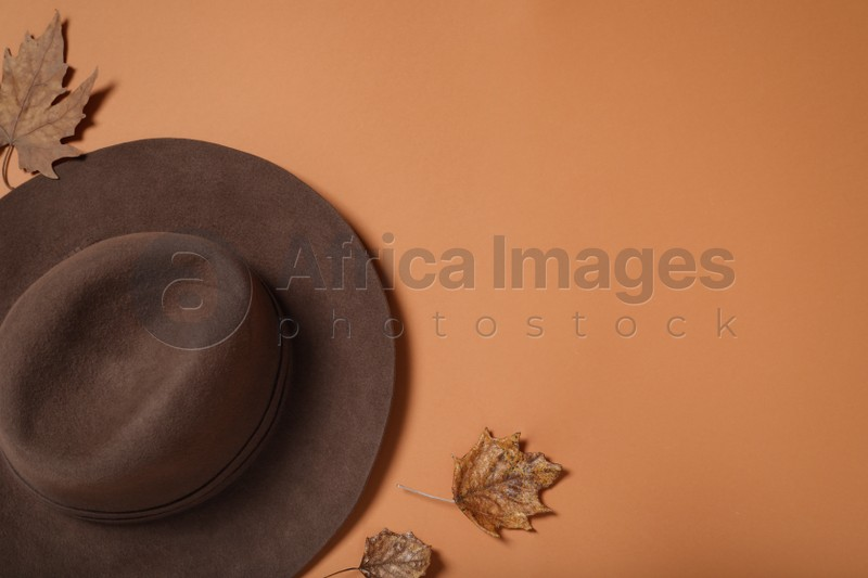 Stylish hat and autumn leaves on orange background, flat lay. Space for text