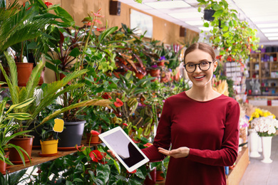 Female business owner with tablet in flower shop