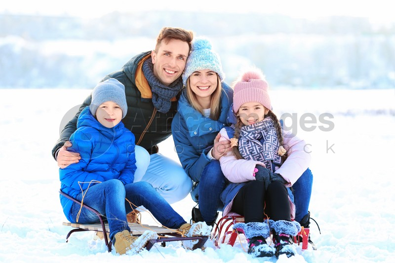 Portrait of happy family with sledge outdoors on winter day