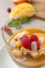 Delicious panna cotta with mango coulis, fresh fruit pieces and almond flakes in bowl, closeup