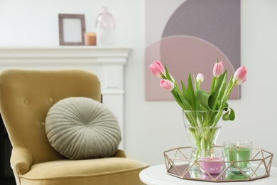 Beautiful tulips and burning candles on white table indoors, space for text. Interior design