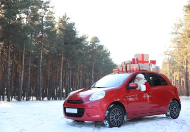 Authentic Santa Claus in red car with gift boxes, view from outside