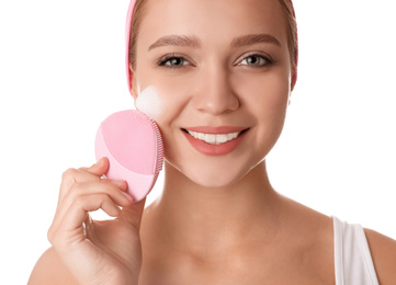 Young woman washing face with brush and cleansing foam on white background. Cosmetic products