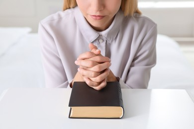 Religious young woman with Bible praying at home, closeup